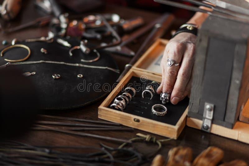 La mano del hombre que pone un anillo en la caja de madera con diversos accesorios imagen de archivo