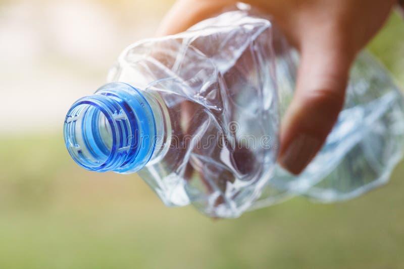 La mano del hombre que sostiene la botella plástica transparente clara lista para reciclar imagenes de archivo