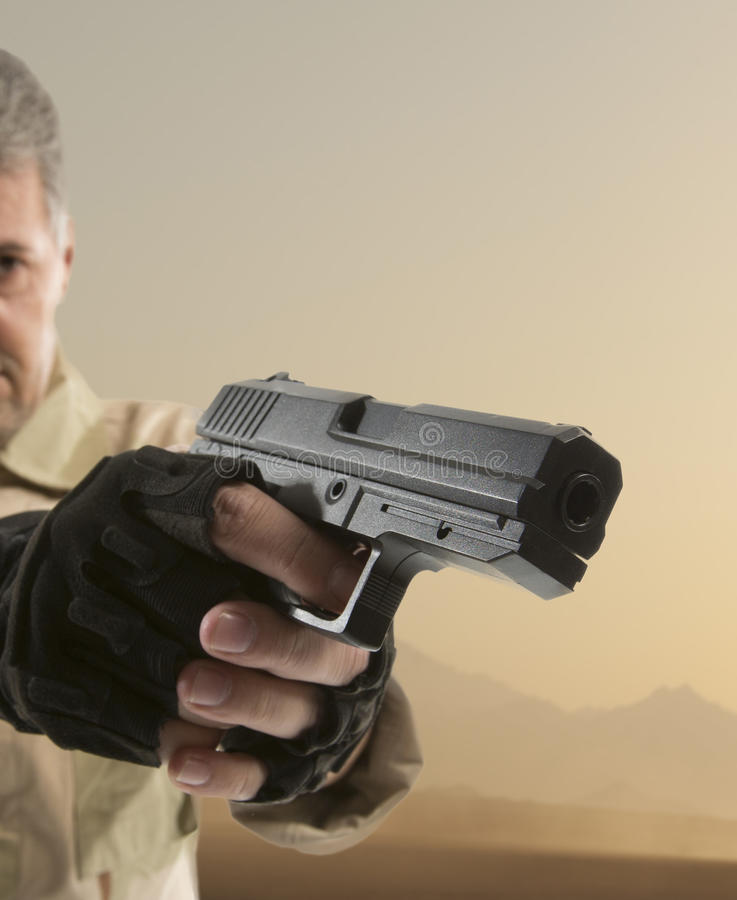 La mano del hombre que sostiene el arma fotografía de archivo libre de regalías