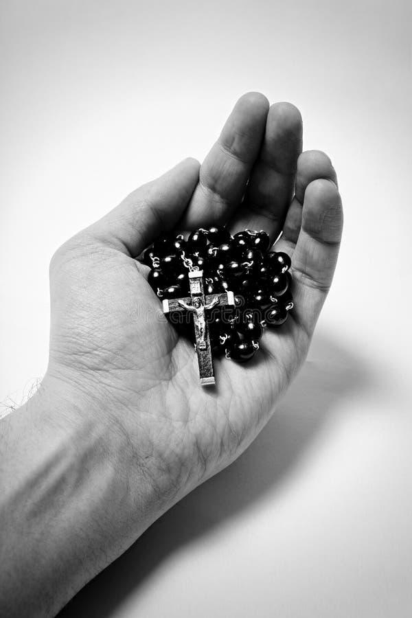 La Mano Del Hombre Que Sostiene El Rosario De Madera Con Crucifijo Católico En Blanco Fotografía de archivo