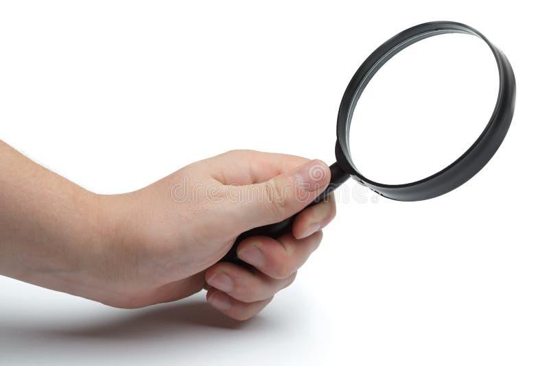 La mano del hombre que sostiene glas que magnifican fotografía de archivo libre de regalías