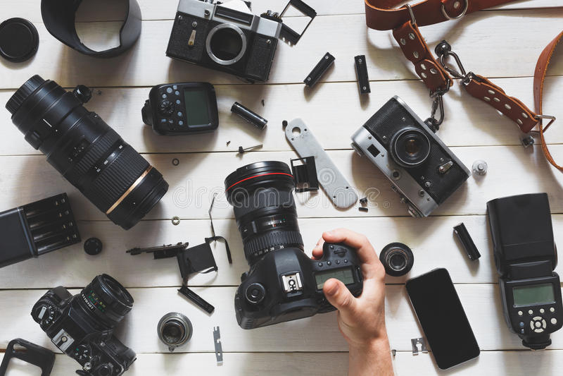 La mano del hombre sostiene la cámara digital en la tabla al lado de las lentes y de los accesorios en el fondo de madera blanco  imágenes de archivo libres de regalías