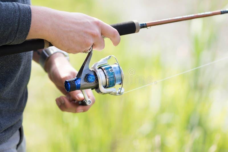 La mano del hombre usando técnica de giro durante la pesca imagen de archivo