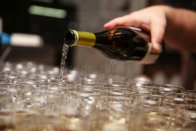 La mano del hombre vierte el vino en los vidrios foto de archivo libre de regalías