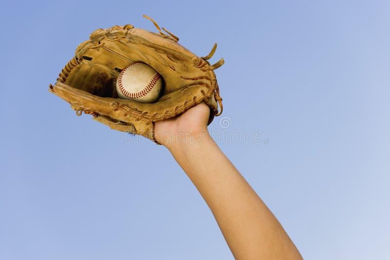 La mano del jugador con el guante y la bola foto de archivo libre de regalías
