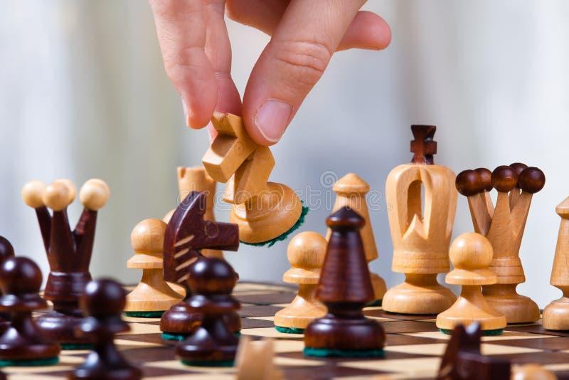 La mano del jugador de ajedrez con el caballero imagenes de archivo