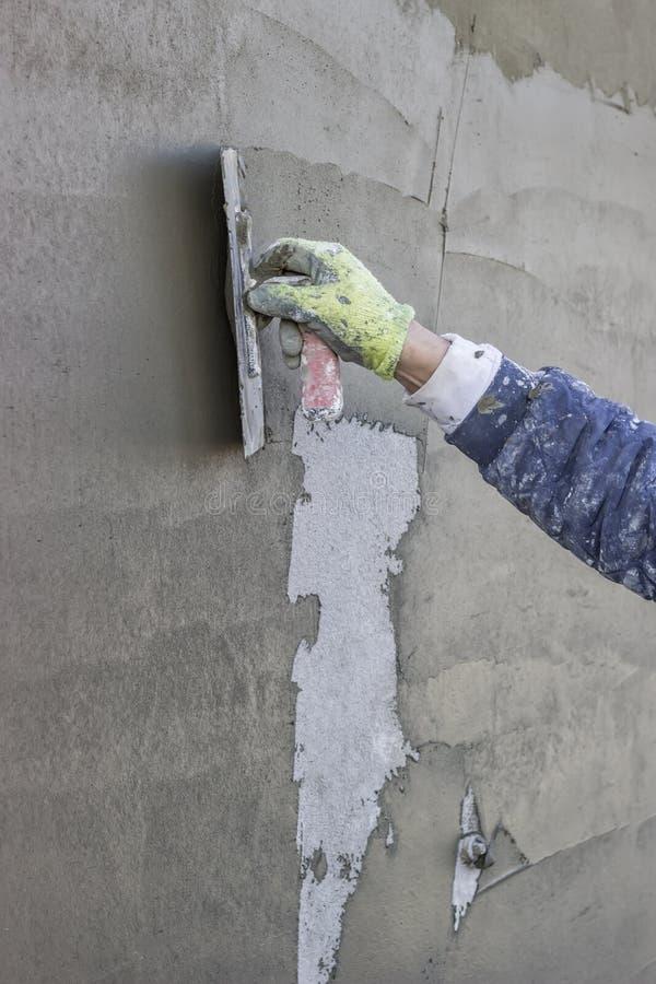 La mano del lavoratore che intonaca una parete esterna fotografia stock libera da diritti