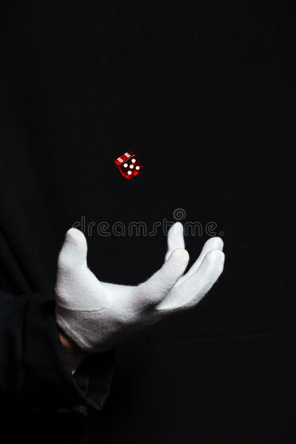 La mano del mago en la demostración blanca del guante engaña con los dados imagen de archivo