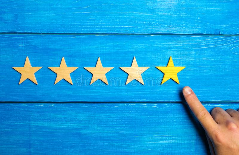 La mano del maschio indica la quinta stella gialla su un fondo di legno blu Cinque stelle Valutazione del ristorante o dell'hotel fotografie stock libere da diritti