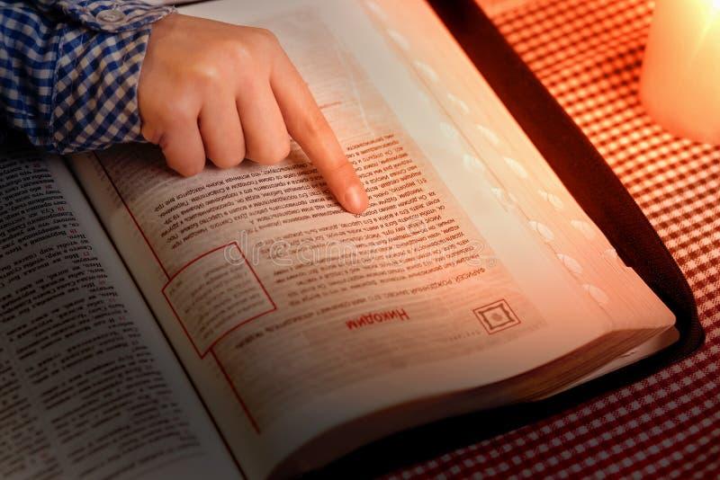 La mano del niño en el libro del evangelio imagen de archivo