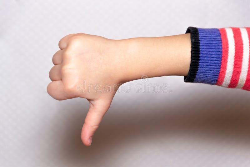 La mano del niño muestra golpe abajo, la muestra del desacuerdo y desemejante negativos foto de archivo