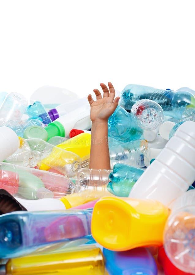 La mano del niño que se pega hacia fuera del plástico embotella la basura imagenes de archivo