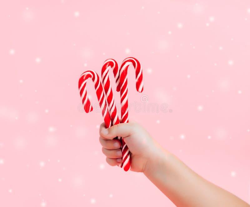 La mano del niño que sostiene los caramelos de la Navidad en fondo rosado imagen de archivo