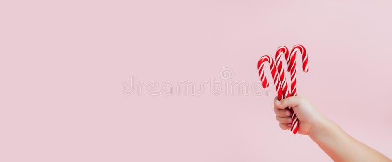 La mano del niño que sostiene los caramelos de la Navidad en fondo rosado fotos de archivo libres de regalías