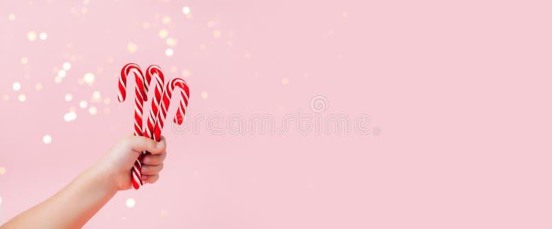 La mano del niño que sostiene los caramelos de la Navidad en fondo rosado fotografía de archivo libre de regalías