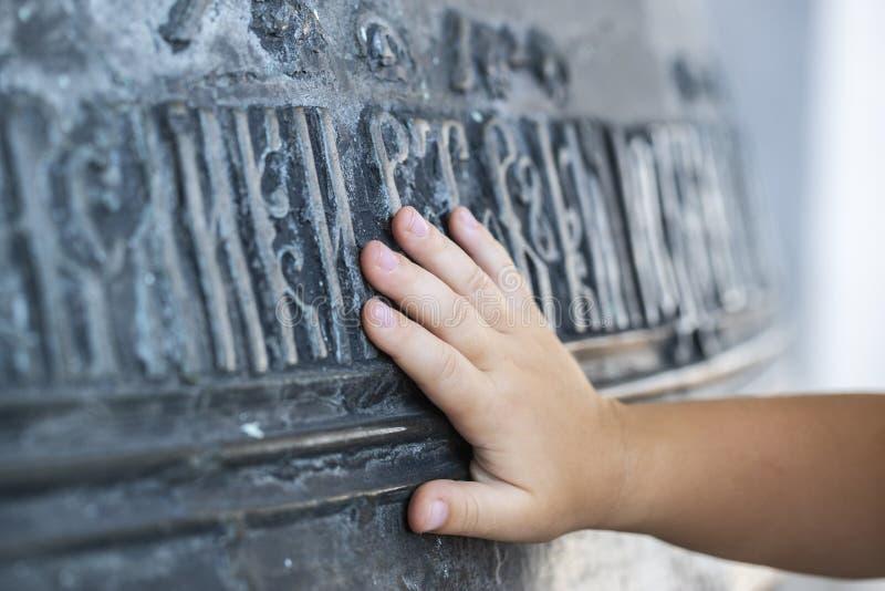 La mano del niño toca una campana de iglesia grande con las inscripciones eslavas antiguas El concepto de espiritualidad Rusia Th fotografía de archivo