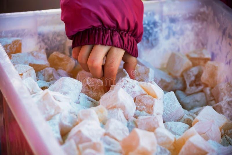 La mano del niño toma lokum del placer turco con el azúcar en polvo imagenes de archivo