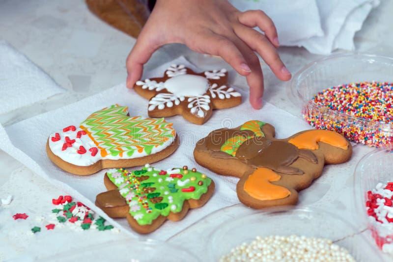 La mano del niño toma o pone en una servilleta blanca una del pan de jengibre de la Navidad con el esmalte Primer imágenes de archivo libres de regalías