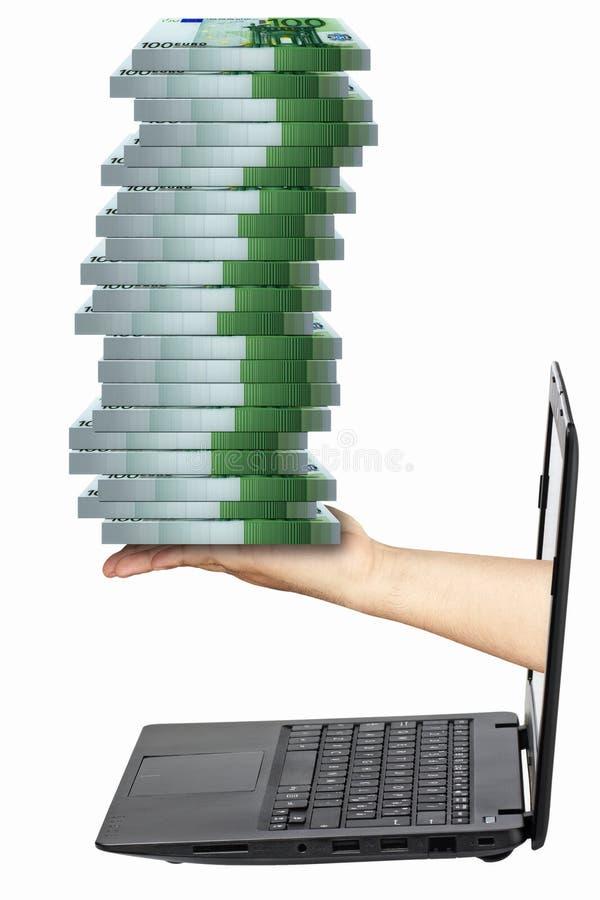 La mano del ordenador portátil embala 100 billetes de banco euro aislados fotografía de archivo libre de regalías