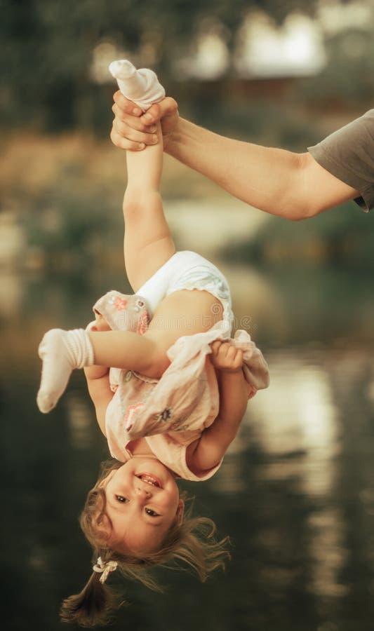 La mano del padre sujeta su pequeña cabeza de la hija hacia abajo imagenes de archivo