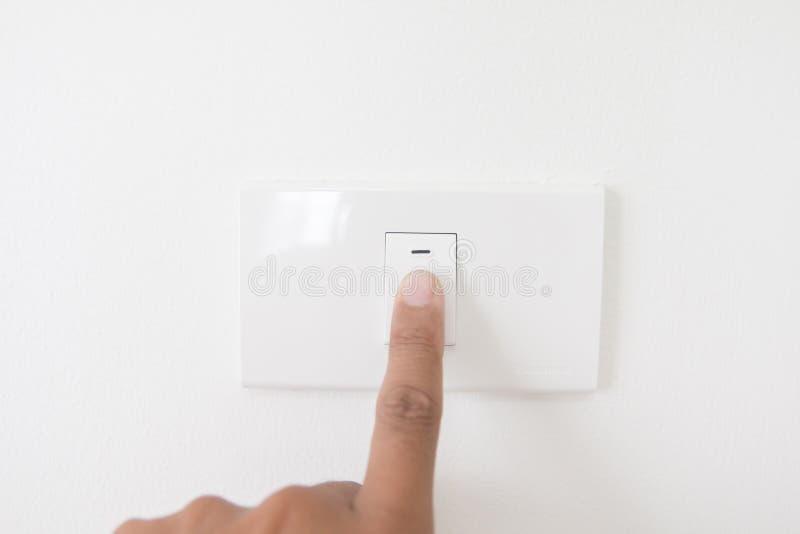 La mano del primer apaga un botón de encendido, botón de la luz de la prensa del finger, mano con el enchufe, botón de encendido  foto de archivo