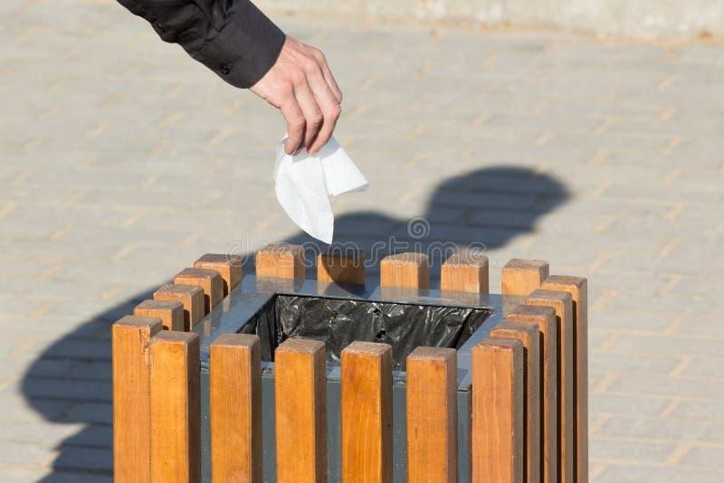 La mano del primer cae el pedazo de basura en bote de basura imagenes de archivo