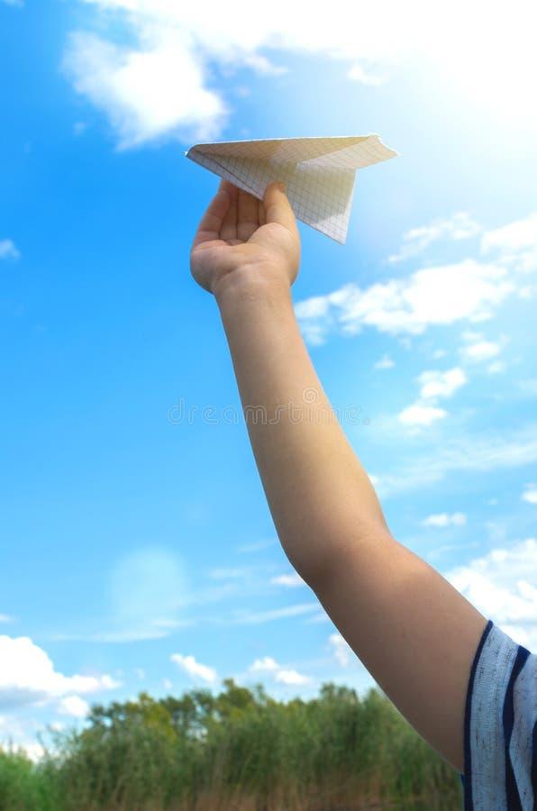 La mano del ragazzino esegue l'aeroplano di carta nel cielo fotografie stock