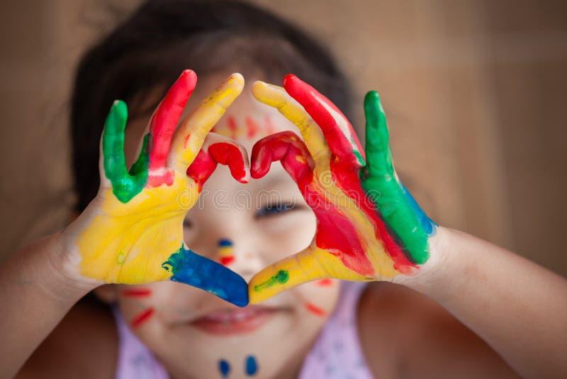 La mano del ` s del bambino con l'acquerello variopinto dipinto fa la forma del cuore immagine stock libera da diritti