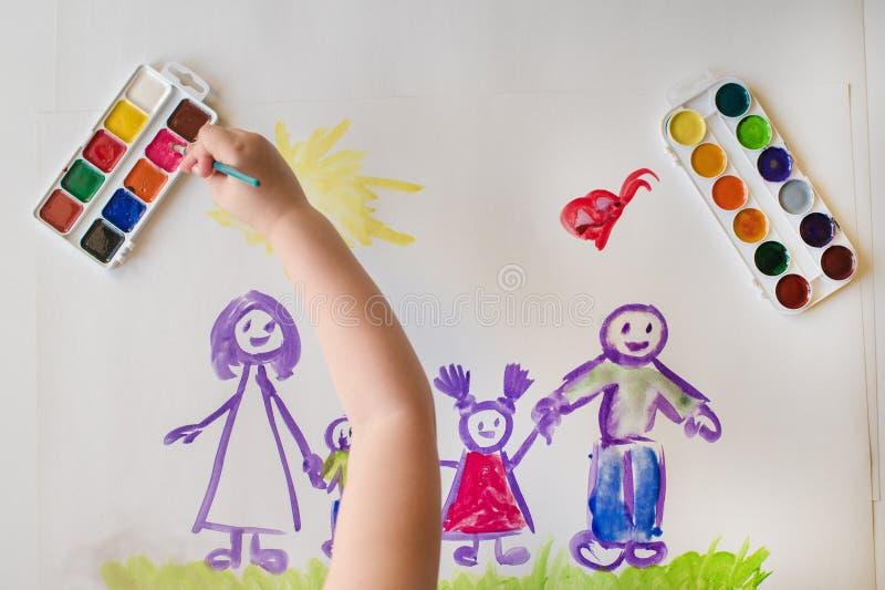 La mano del ` s del bambino dipinge una famiglia felice immagine stock