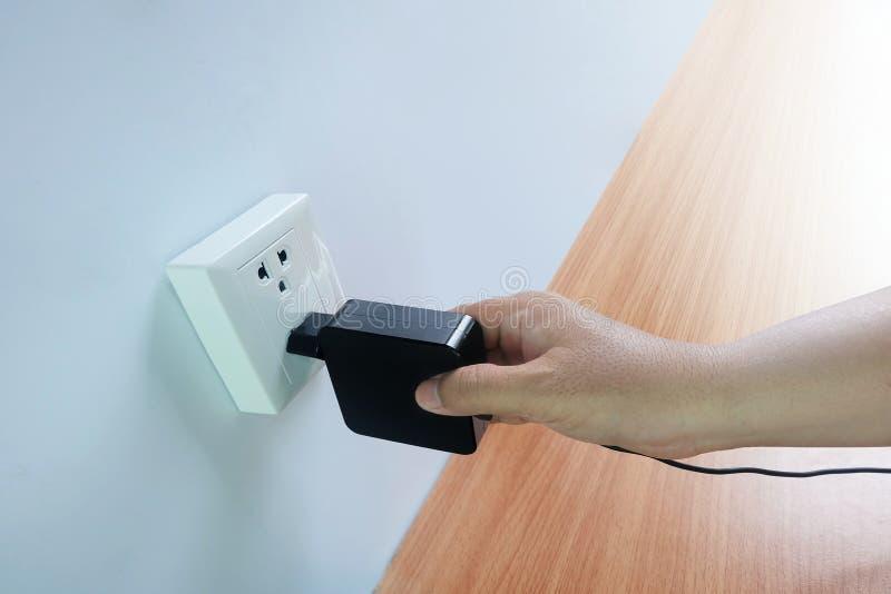 La mano del ` s de los hombres tiene enchufes, adaptadores, enchufes del cable eléctrico, dispositivos en piso de madera foto de archivo libre de regalías