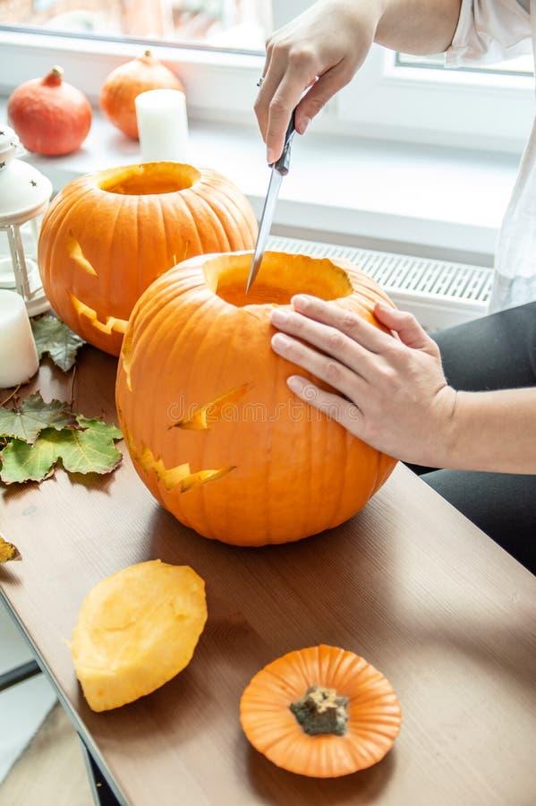 La mano del ` s de la mujer con el cuchillo corta la calabaza para Halloween imagenes de archivo