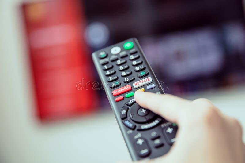 La mano del ` s de la mujer está sosteniendo una TV teledirigida con fluir medios servicios fotografía de archivo