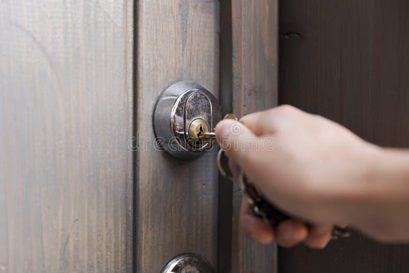 La mano del ` s de la mujer pone la llave en el ojo de la cerradura de la puerta de madera SE del hogar fotos de archivo libres de regalías