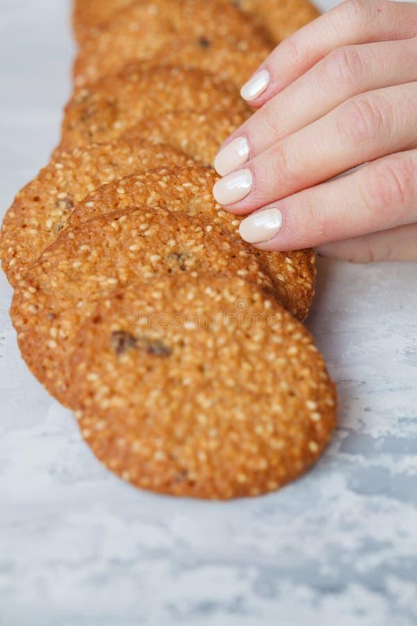 La mano del ` s de la mujer toma una galleta sana redonda hecha del sésamo blanco fotografía de archivo libre de regalías
