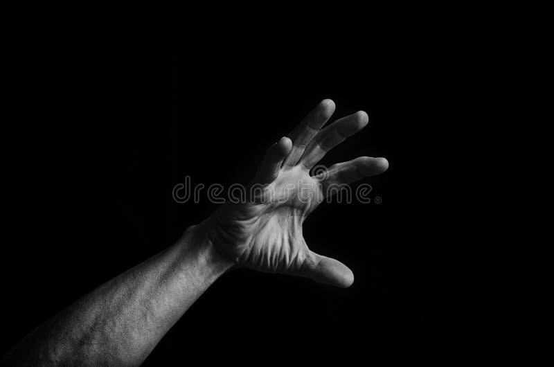 La mano del ` s degli uomini raggiunge su dall'oscurità alla luce immagini stock