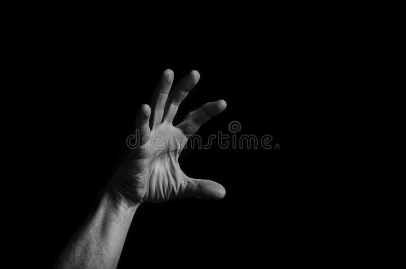 La mano del ` s degli uomini raggiunge su dall'oscurità alla luce fotografia stock libera da diritti