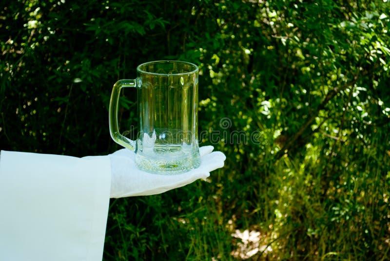La mano del ` s del cameriere in un guanto bianco tiene un vetro di birra contro lo sfondo della natura immagini stock