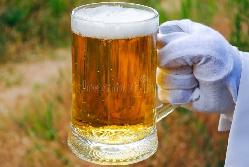 La mano del ` s del cameriere in un guanto bianco tiene un vetro di birra contro lo sfondo della natura fotografia stock libera da diritti