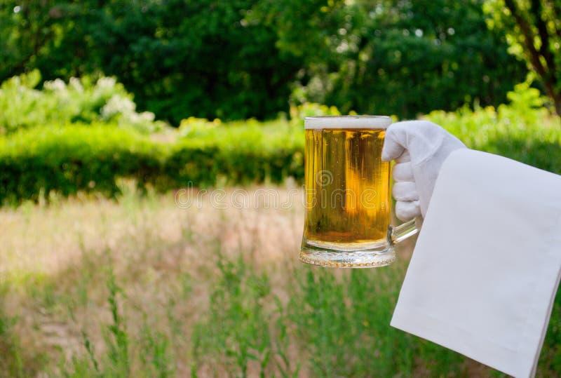 La mano del ` s del cameriere in un guanto bianco tiene un vetro di birra contro lo sfondo della natura fotografia stock