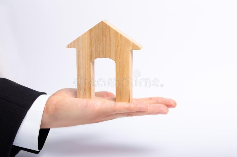 La mano del ` s dell'uomo d'affari allunga una casa di legno con una grande entrata Il concetto del bene immobile commerciale, l' immagini stock