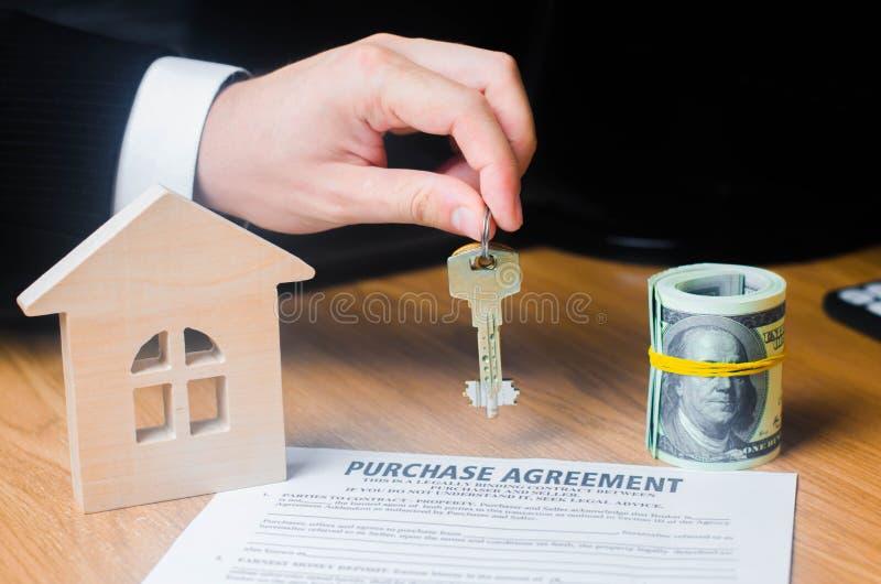 La mano del ` s dell'uomo d'affari tiene le chiavi al contratto per l'acquisto della proprietà o del bene immobile Concetto del c fotografie stock libere da diritti