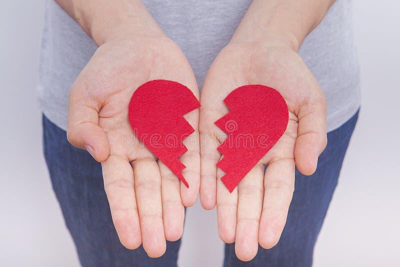 La mano del ` s della donna sta tenendo il cuore rosso rotto immagini stock
