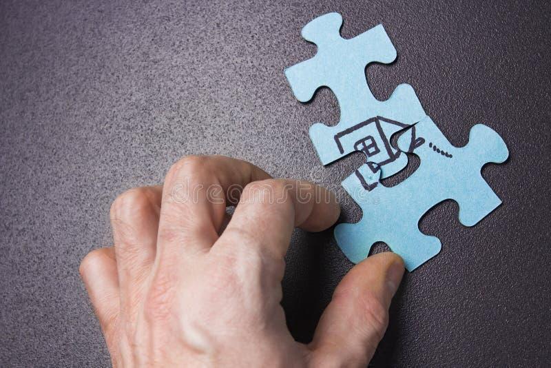 La mano del ` s della persona accatasta sul puzzle con il primo piano della casa Casa di concetto Assicurazione domestica e del c immagini stock