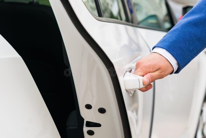 La mano del ` s della persona tiene la maniglia della porta di automobile ed apre l'automobile, primo piano immagini stock libere da diritti