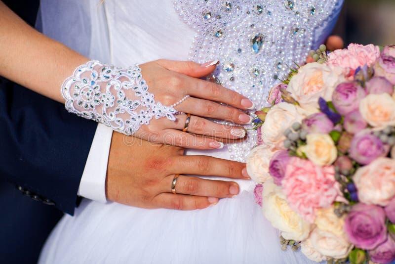 La mano del ` s dello sposo con un anello abbraccia la vita del ` s della sposa, le tenute della sposa la mano del ` s dello spos immagine stock libera da diritti