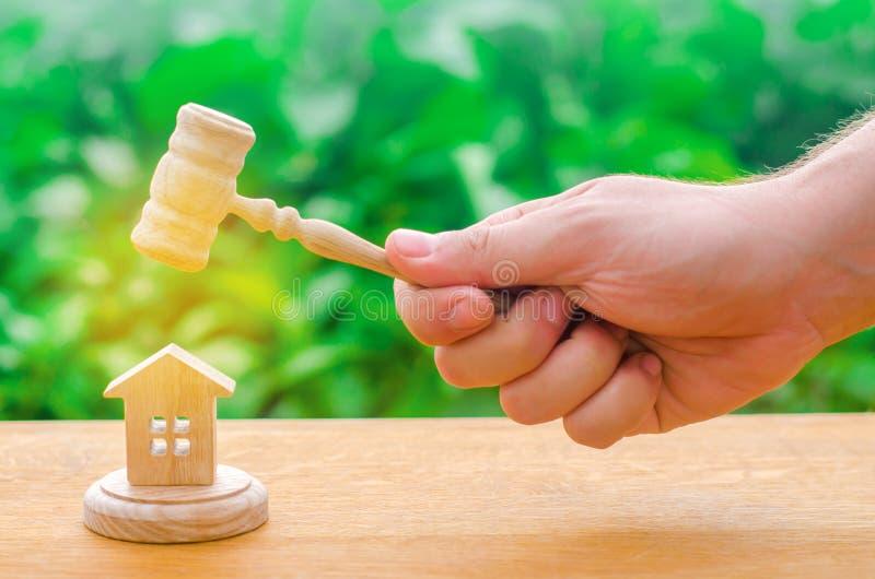 La mano del ` s del giudice sta tenendo un martello accanto alla casa di legno prova del bene immobile Eliminazione ed alienazion immagine stock libera da diritti