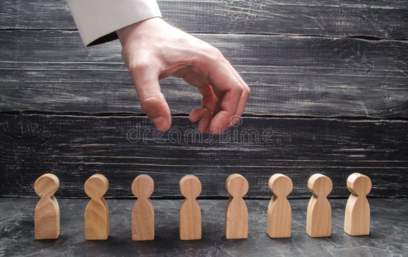 La mano del ` s del hombre de negocios cuelga sobre las figuras de la gente y la prepara para asir El despido de trabajadores, la foto de archivo libre de regalías