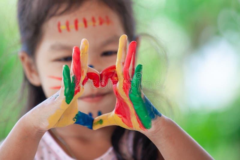 La mano del ` s del niño con la acuarela colorida pintada hace forma del corazón imagenes de archivo
