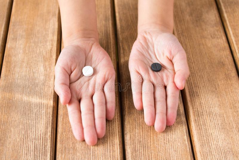 La mano del ` s del niño con las píldoras blancos y negros en fondo de madera imagenes de archivo