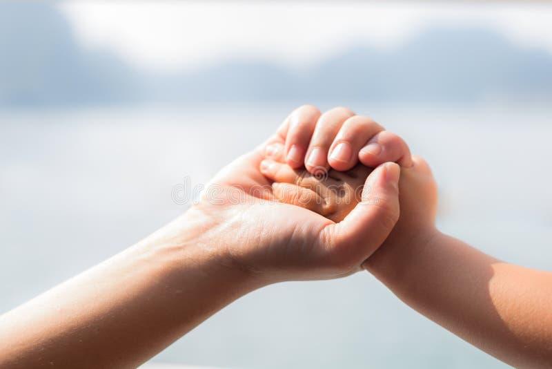 La mano del suo bambino della tenuta della madre tenuta, fine su fotografia stock